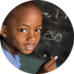 A young boy in a developing country writing on a chalkboard