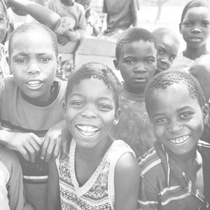 A group of smiling children in a developing country that benefited from monthly giving to Cross Catholic Outreach