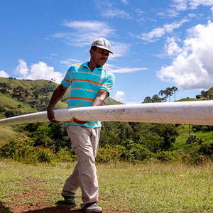 A worker in a rural, developing country carrying a pipe to build a water system