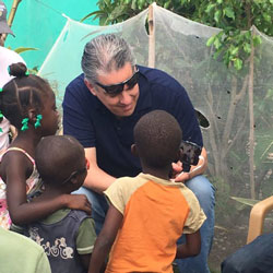 Radio personality Drew Mariani shares images on his tablet with Haitian children