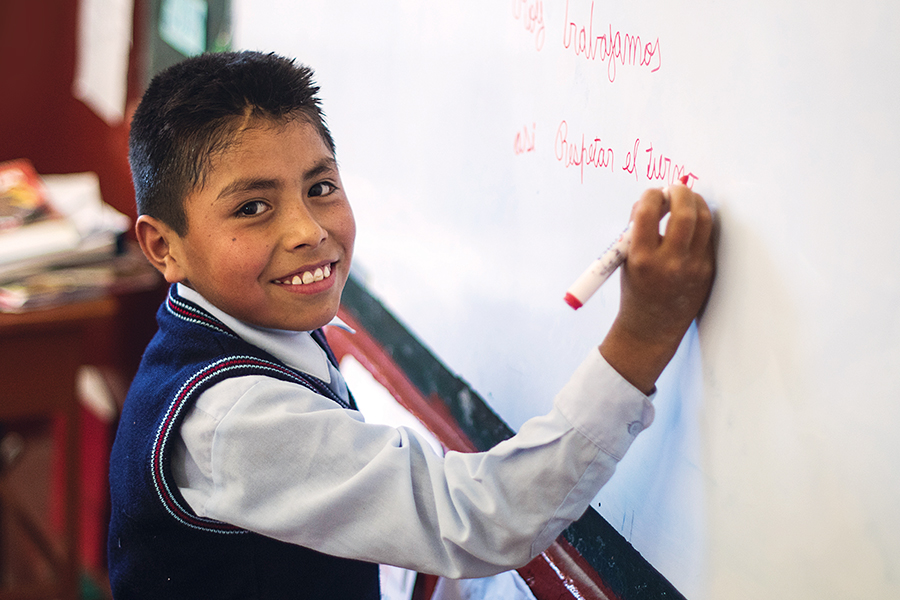 Percy Quispes, from the mountain village of Andamarca, Peru, writing on whiteboard at a school
