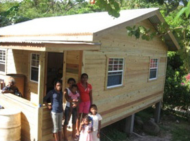 The Mahons proudly stand in front of an answer to their prayers—a beautiful new home!
