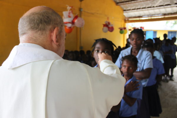 Fr. Glenn Meaux giving Holy Communion to primary school students at the Kobonal Haiti Mission.