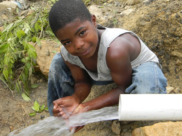 In the rural community of La Patilla, a Dominican boy catches a handful of clean, refreshing water from the new aqueduct system provided by Cross Catholic Outreach and the Diocese of San Juan de la Maguana. Access to clean water prevents illness, improves hygiene, sustains agricultural development and boosts a community's overall quality of life.