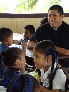 Fr. Montalvo visits Santa Rosa school children during their Cross Catholic-funded lunch.