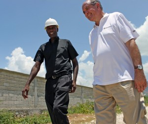 Cross Catholic President Jim Cavnar (right) and Msgr. Jean Pierre (left) examine the newly finished security wall of a health clinic being built in Haiti.