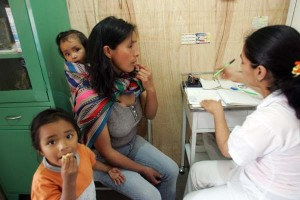 A Peruvian nurse gives checkups to a needy mom and her two kids outside Lima. The free clinic is run by Catholics in Peru, and sponsored by Cross International Catholic Outreach.