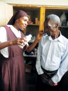 Sr. Irene takes care of a sick villager at her Cross Catholic supported medical clinic.