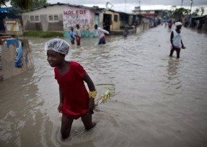 People walk in a flooded street in the neighborhood of Cite Soleil in Port-au-Prince, Haiti, on Nov. 6, 2010 after Hurricane Tomas passed through the area. Photo courtesy of Ramon Espinosa, Associated Press.
