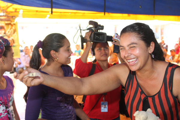 A TV camerawoman looks on as a beneficiary holds a slip of paper indicating the house that will be hers.