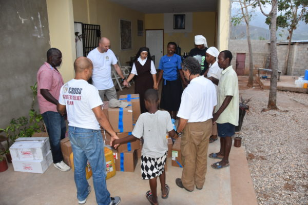 Cross Catholic Outreach's disaster response team prays with Haitian survivors of Hurricane Matthew while delivering aid to a mission of the Compassionate Franciscan Sisters of the Poor.