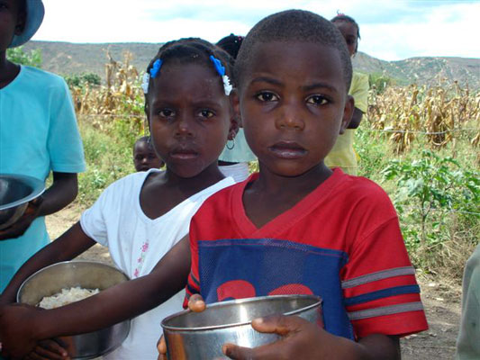 A Haitian boy and girl stand with bowls of rice