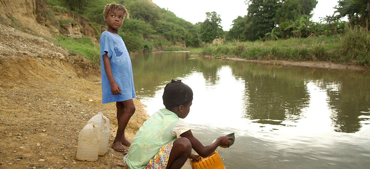 Two children gathering water from a dirty stream near Kobonal, Haiti