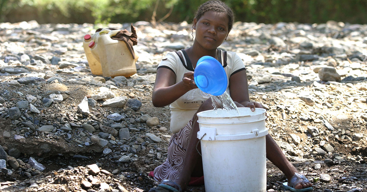 A woman in need collects water