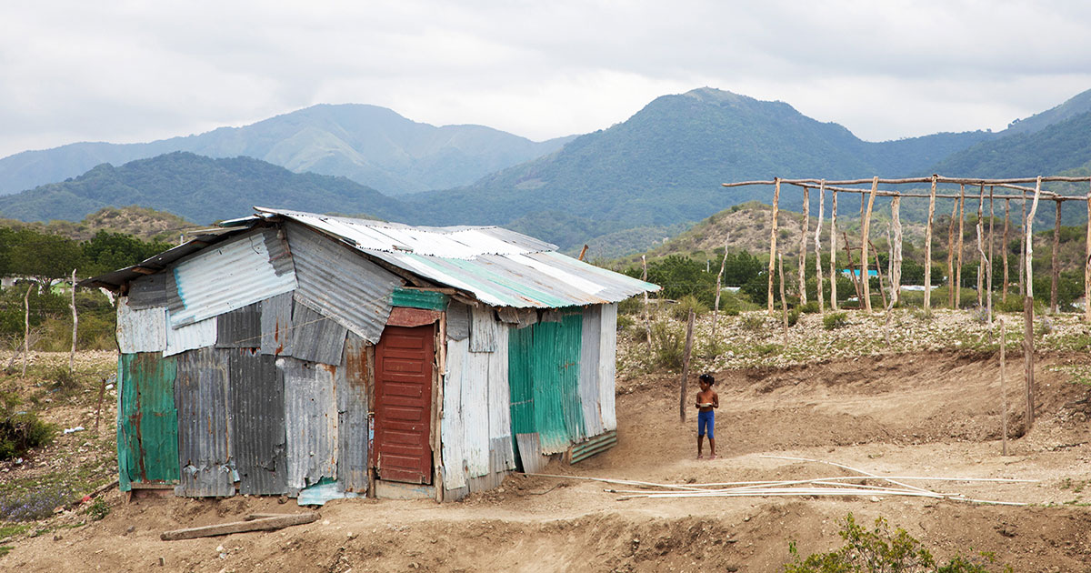 child stands outside vulnerable shanty housing structure