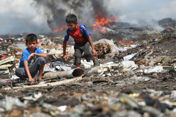 Children foraging through a dump in Guatemala. Trash is on fire in the background
