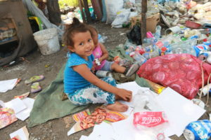 Young girl searches through trash in Guatemala