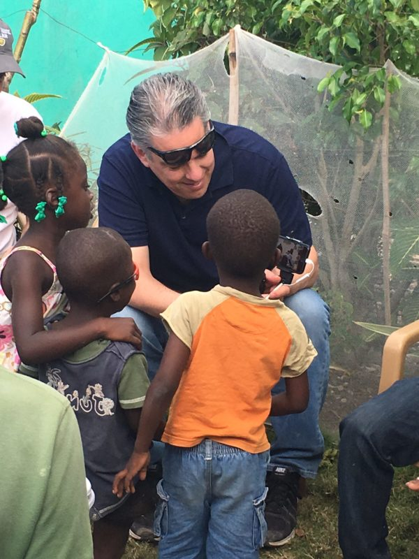 Radio personality Drew Mariani shares images on his tablet with Haitian children.