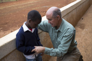 Cross Catholic Outreach President Jim Cavnar prays with a young boy during a recent trip to Kenya.