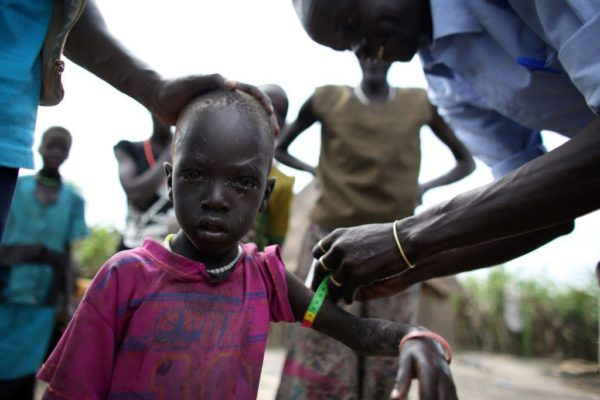 A medical worker measures a Sudanese child for malnutrition.]