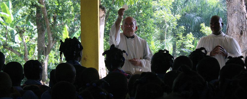 Priest raises the Eucharist at Mass.