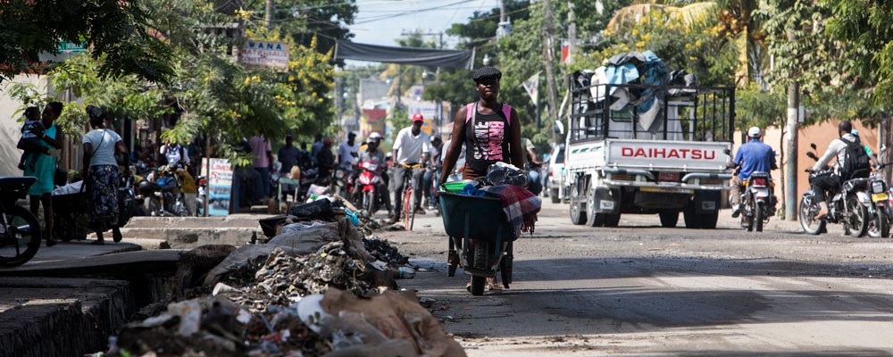 Trash is piled on the side of the road in a Haitian slum