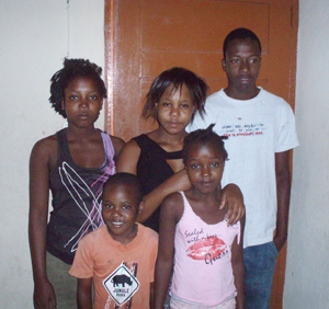 The Borjes children, now ages 7 to 20, stand in front of their new home built through the gifts of our benevolent donors.