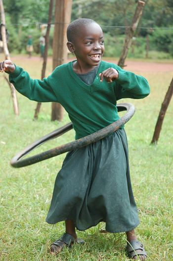 Daisy, a former street child who lives at St. John Bosco, shows off her hula hooping skills with an old bike tire.