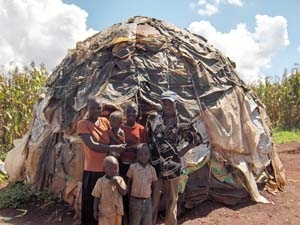 A family of the Turkana tribe stands in front of their igloo-like hut made of garbage scraps—the typical home of students at St. John Bosco Rehabilitation Center in Kitale, Kenya.