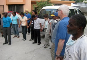 The staff and volunteers at Hospital Espoir offer a prayer thanks as the medical supplies from Cross International Catholic Outreach arrive.