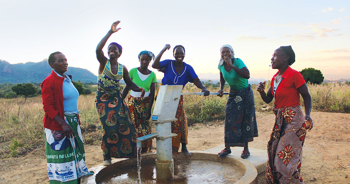 women collecting water from a new well