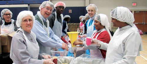students and volunteers at a food packing event