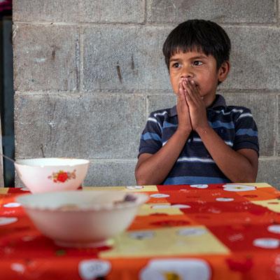 A boy prays before eating
