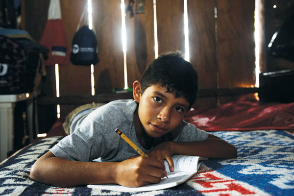 A child does homework on his bed in a dilapidated house