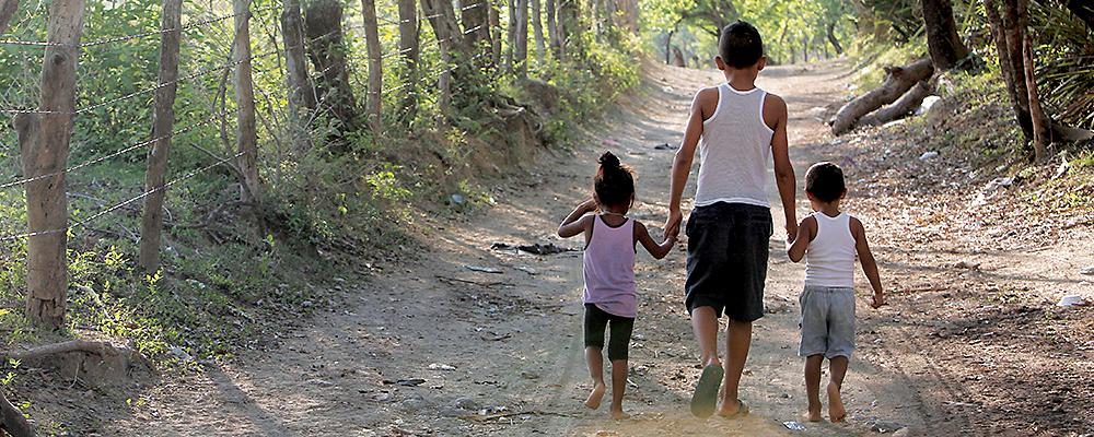 Poor family walking in the road
