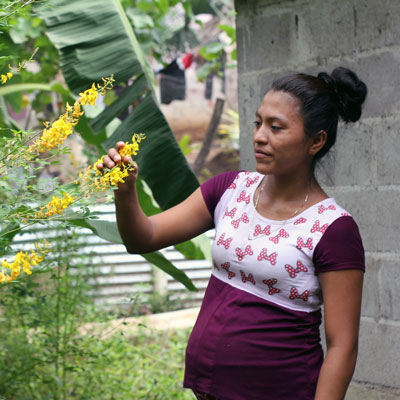 A pregnant mother inspects a flowering plant