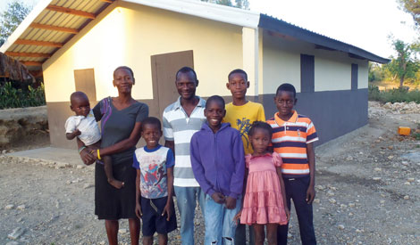 family standing in front of their new house