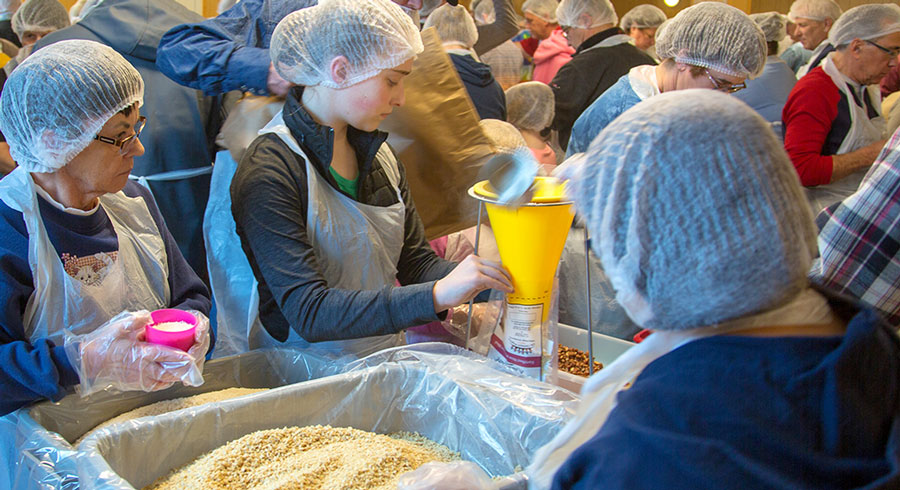 Students and volunteers packing food for the poor