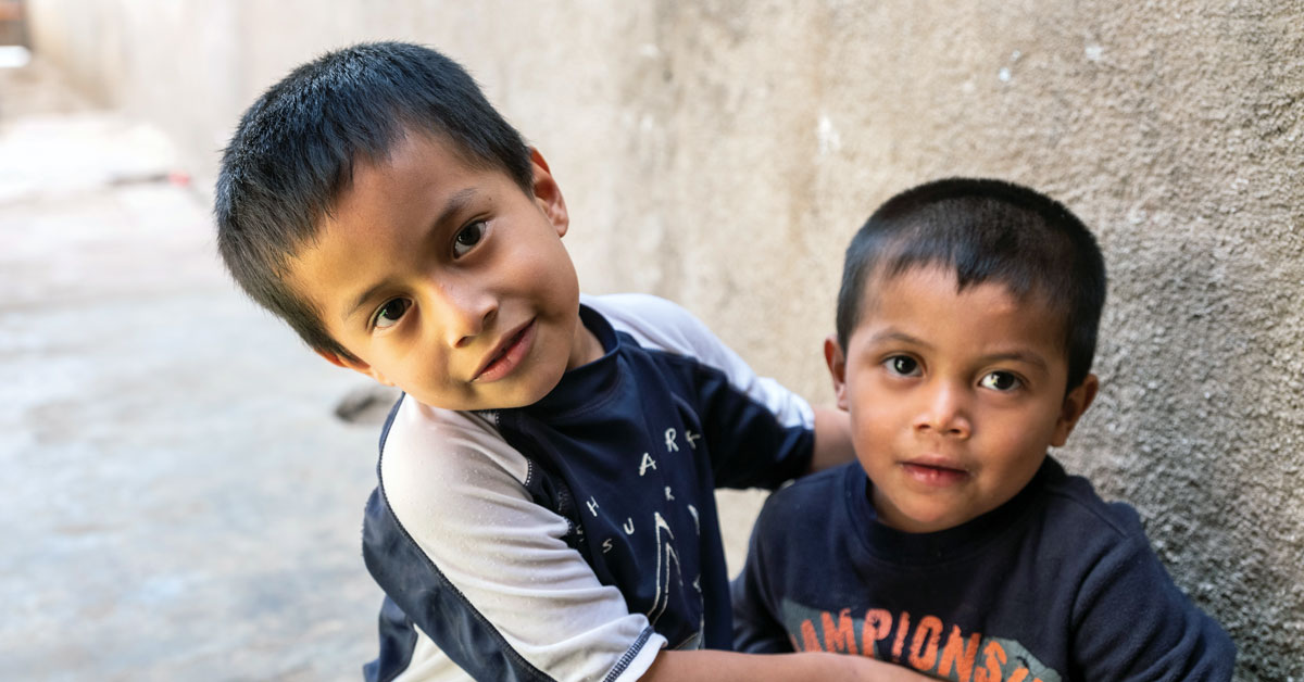 Two young boys in a narrow alleyway.