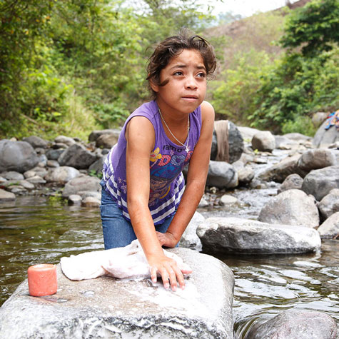 Guatemalan child gathering water from stream
