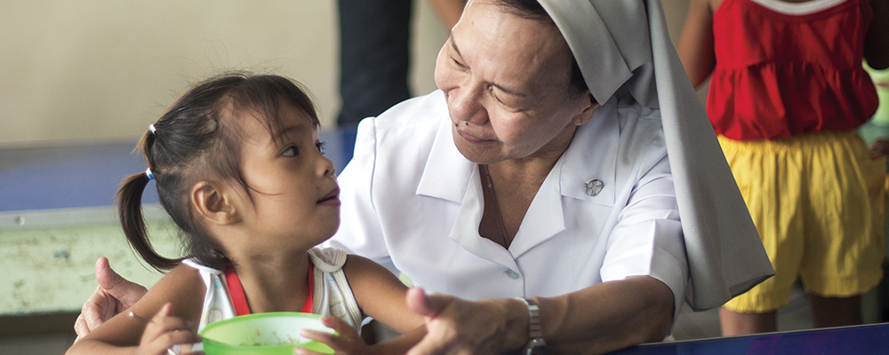 A religious sisters provides a nourishing meal to a child in the Philippines