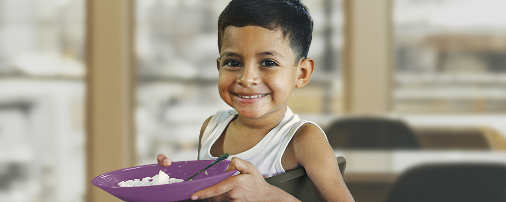 A smiling child hold a bowl of nutritious food