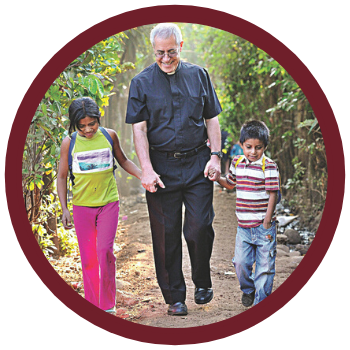 Father Raul Monterroso holds the hands of children in the Diocese of Santa Rosa de Lima in Guatemala