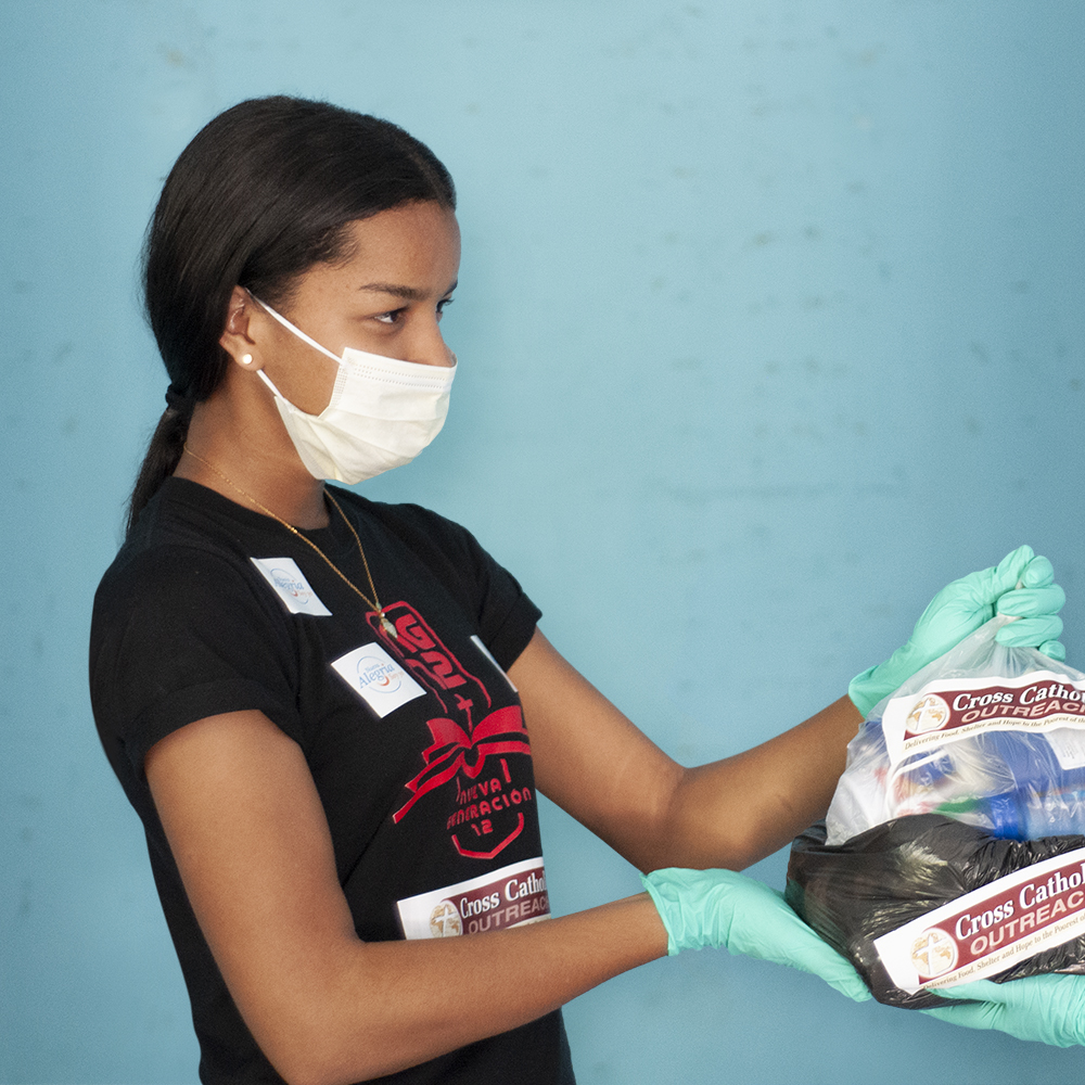 A volunteer in the Dominican Republic handles a hygiene pack for distribution to the poor.