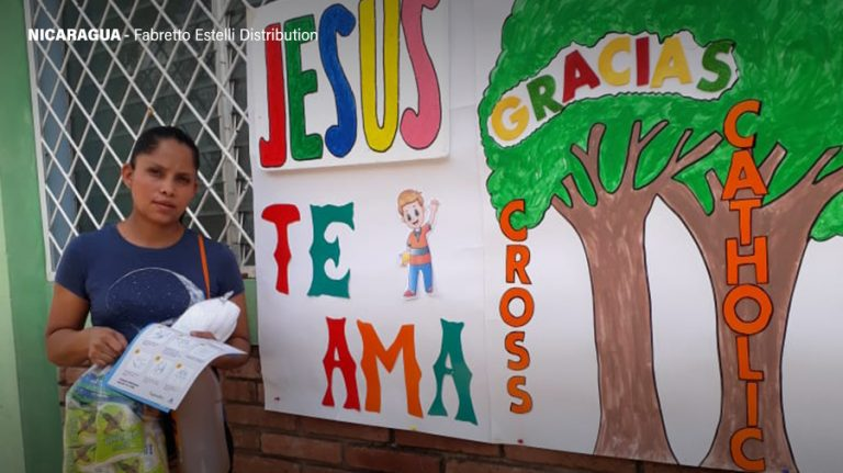 A grateful recipient of the Fabretto Estelli distribution stands in front of a sign thanking Cross Catholic Outreach