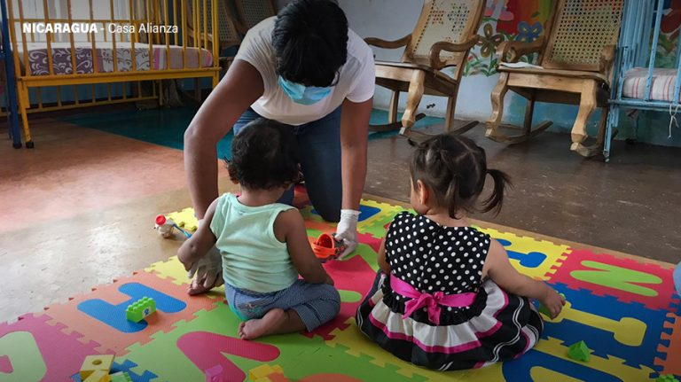 A woman plays with two small children at Casa Alianza in Nicaragua