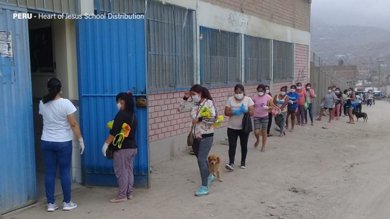 Families wait in line for a food distribution at Heart of Jesus School in Peru