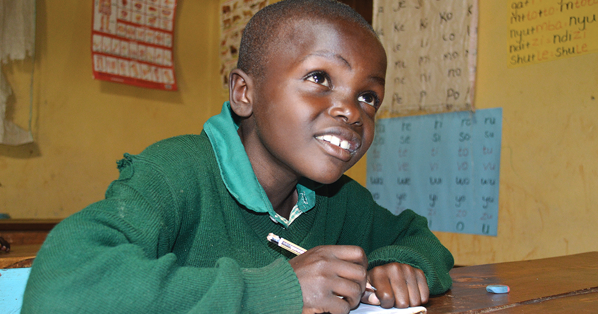 In a classroom, Cedric Shadrack, a student at St. John Bosco's in Kenya, completes a school assignment