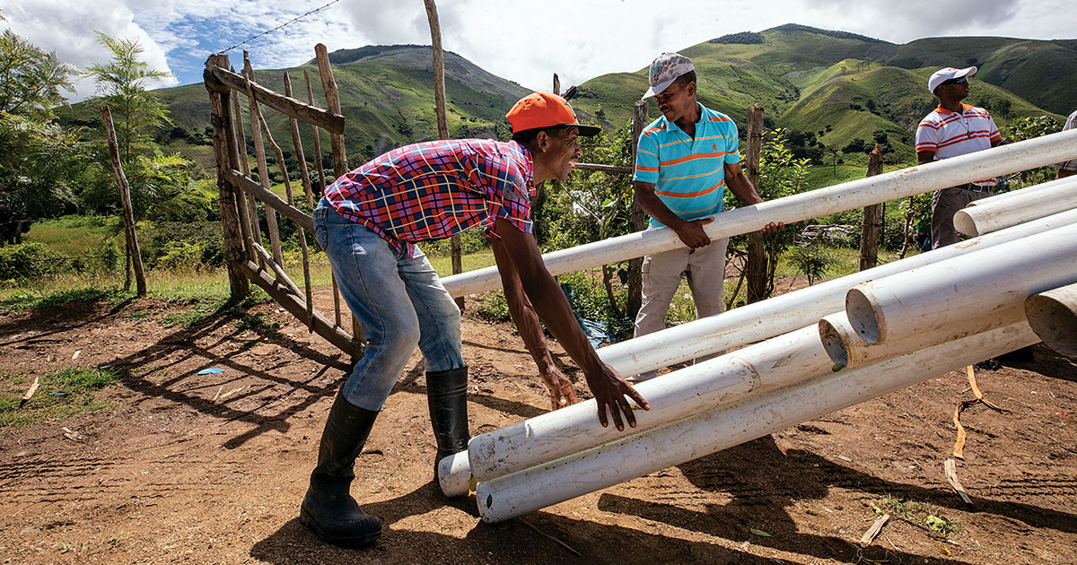 A man in the Dominican Republic holding PVC pipes
