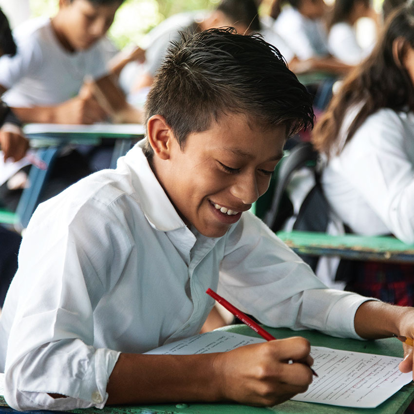 A student at a school in Santa Rosa de Lima in Guatemala smiles as he completes his schoolwork